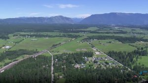 The Right Place video screenshot of green trees, fields and mountains with houses.