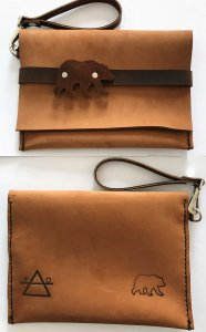 Tan leather clutch with brown leather grizzly bear and strap front and back