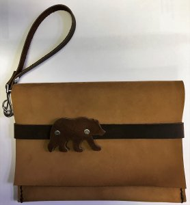 Tan leather clutch with brown leather grizzly bear and strap