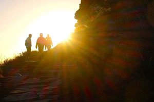 Hikers at sunset in silhouette against bright sun
