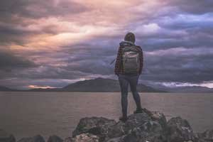 Hiker looking out at lake and mountains on a stormy cloudy day; Donate Time